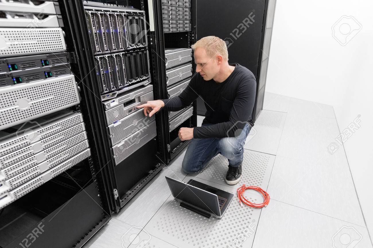 It engineer or consultant working with backup server. Shot in data center. Stock Photo - 27864148