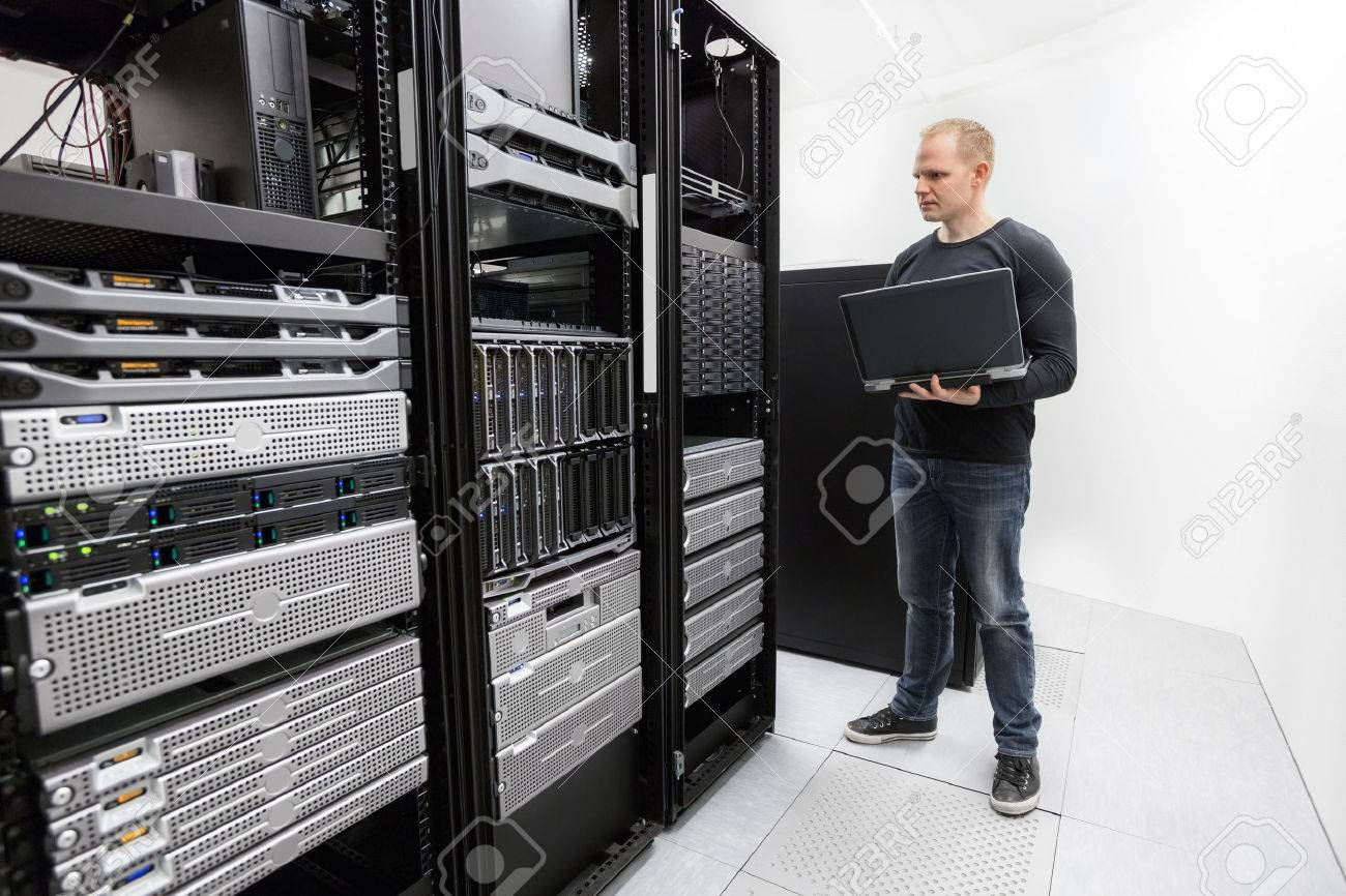 It engineer or consultant standing with a laptop and monitor blade servers in data rack. Shot in datacenter. Stock Photo - 27864150