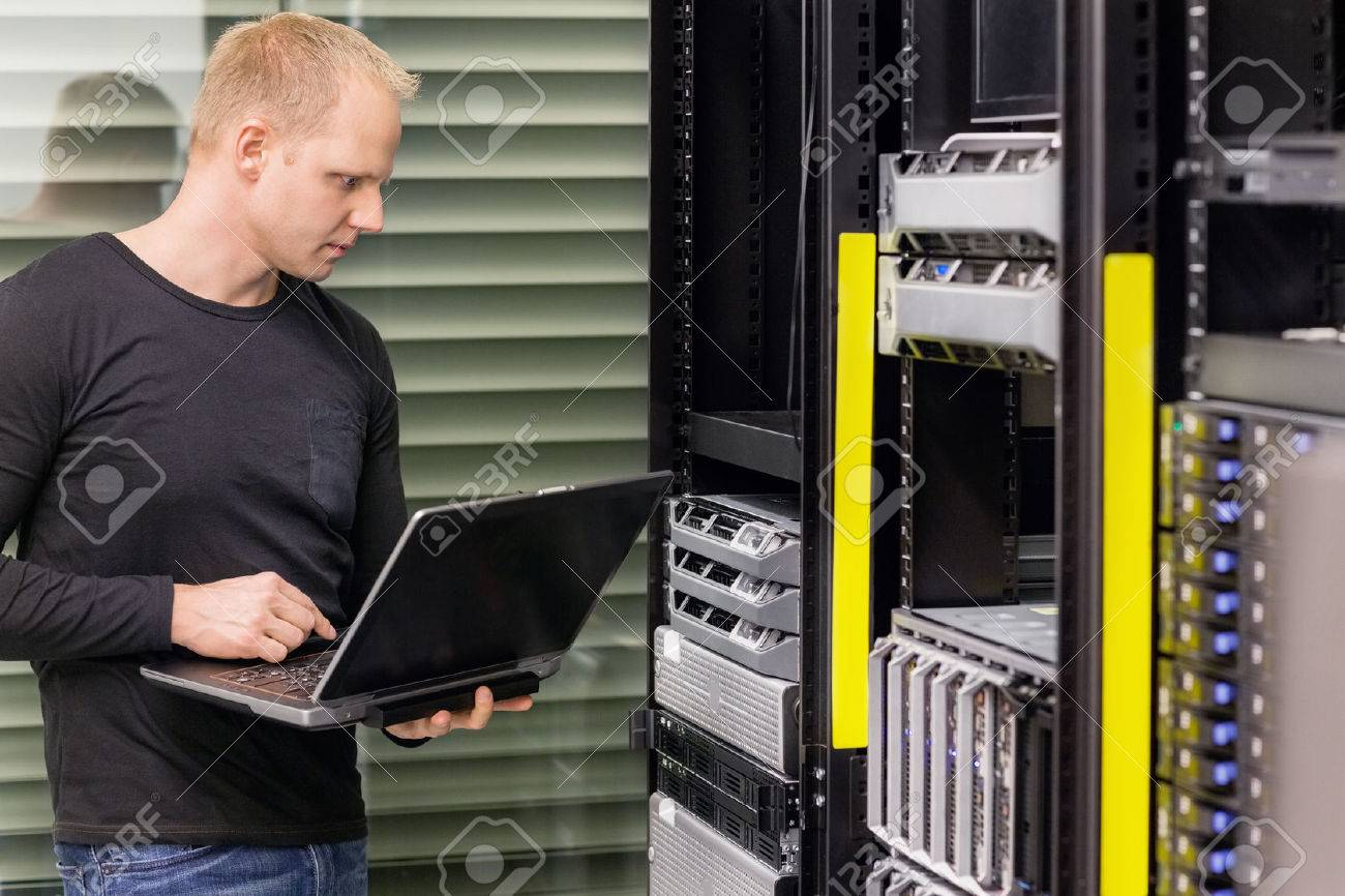 It engineer or consultant standing with a laptop and monitor blade servers in data rack. Shot in datacenter. Stock Photo - 27864156