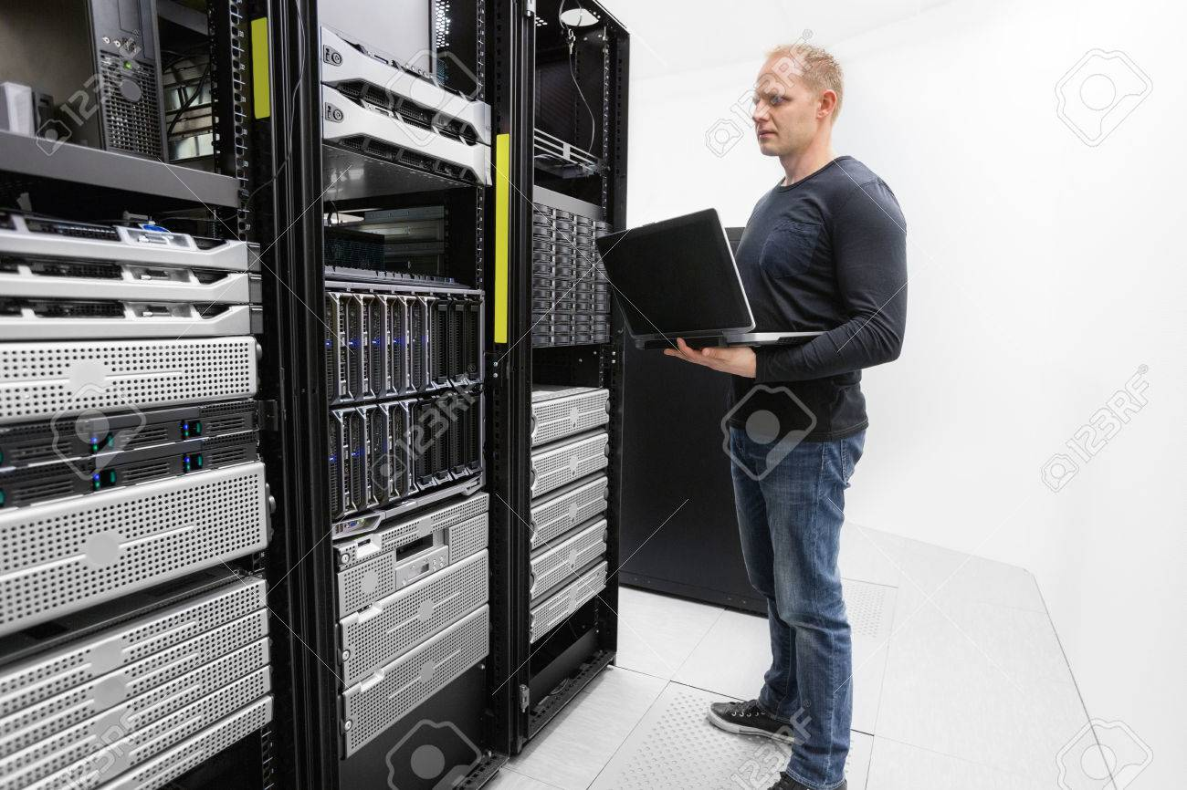 It engineer or consultant standing with a laptop and monitor blade servers in data rack. Shot in datacenter. Stock Photo - 27864165