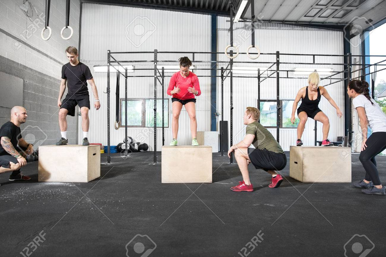 A group trains box jump with personal trainers at a cross fit center. Stock Photo - 29283241