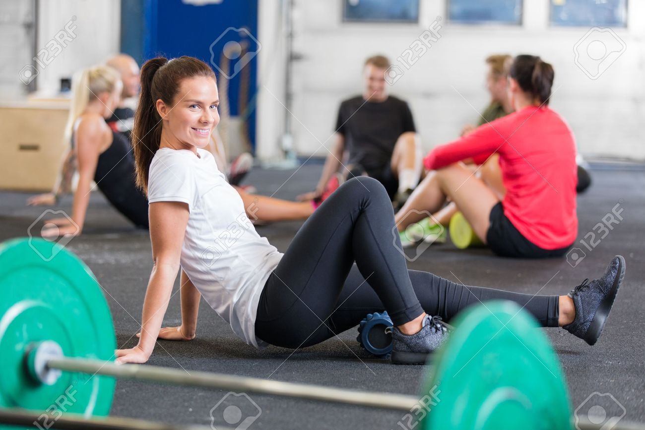 Smiling woman doing cross fit exercise for flexibility and mobility using a yoga fitness foam roller. Stock Photo - 29285925