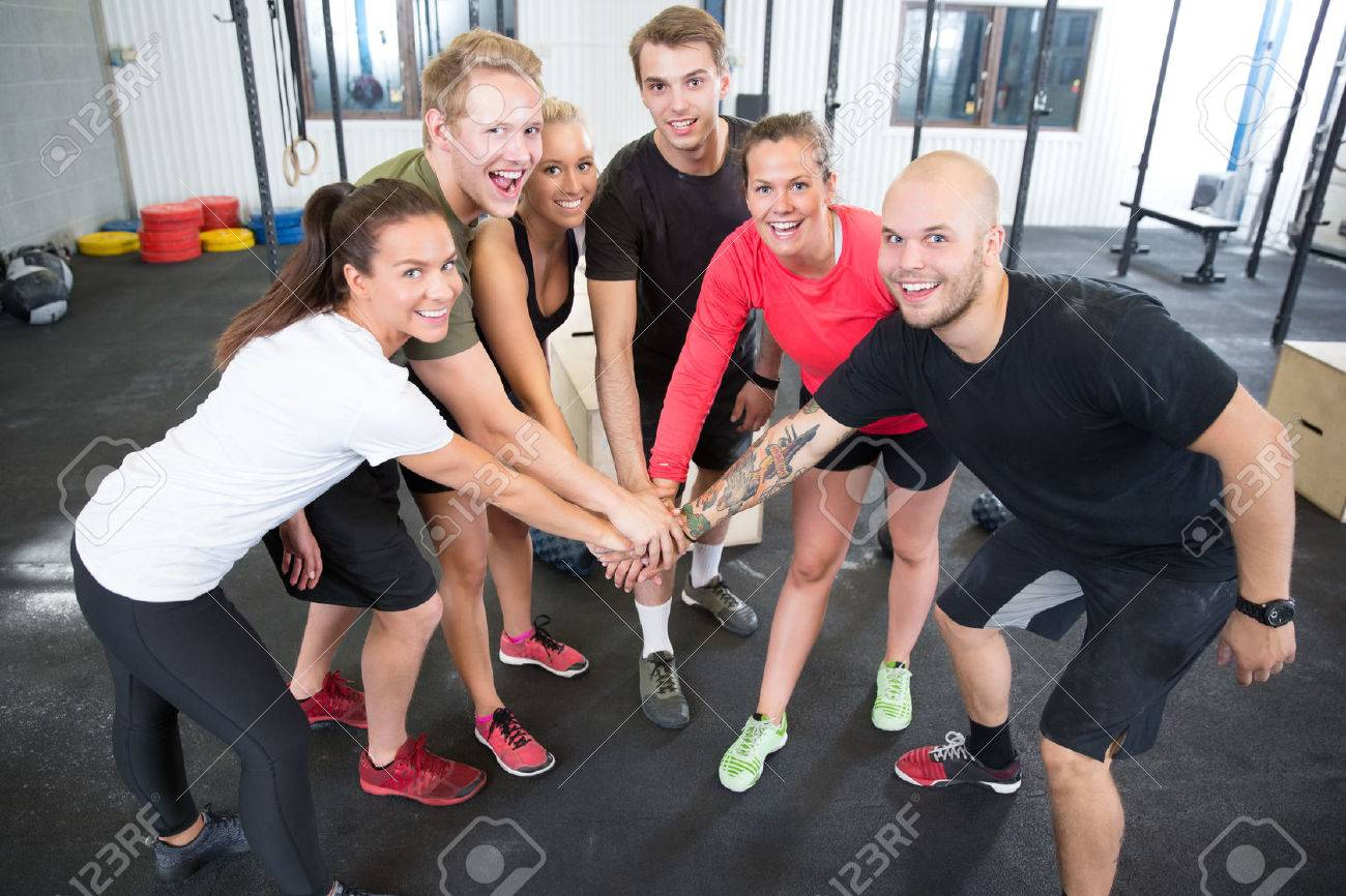 Happy And Smiling Crossfit Workout Group Holding Hands At The Gym Center Stock Photo