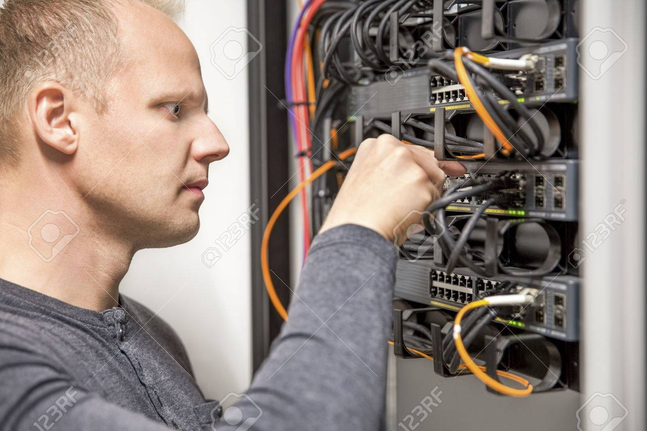 IT consultant connecting network cable into switch Stock Photo - 33033792