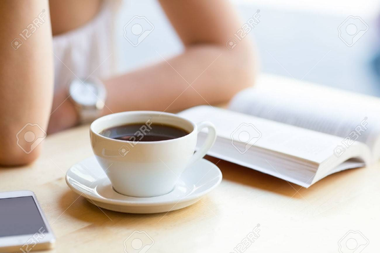 Woman reading book and drinking coffee at cafe Stock Photo - 33575725