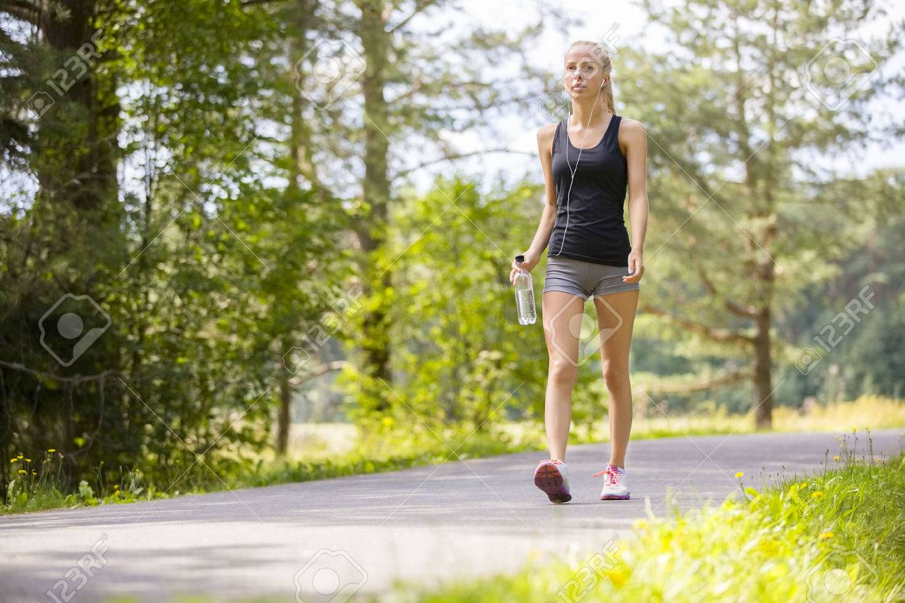 Beautiful young and fit blonde woman walking on trail in the woods. Workout outdoor. Stock Photo - 45840274