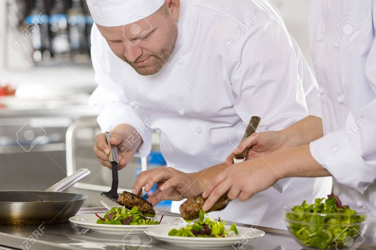Smiling chef and his assistant prepare meat dish in a professional kitchen at restaurant or hotel. Stock Photo - 46574509