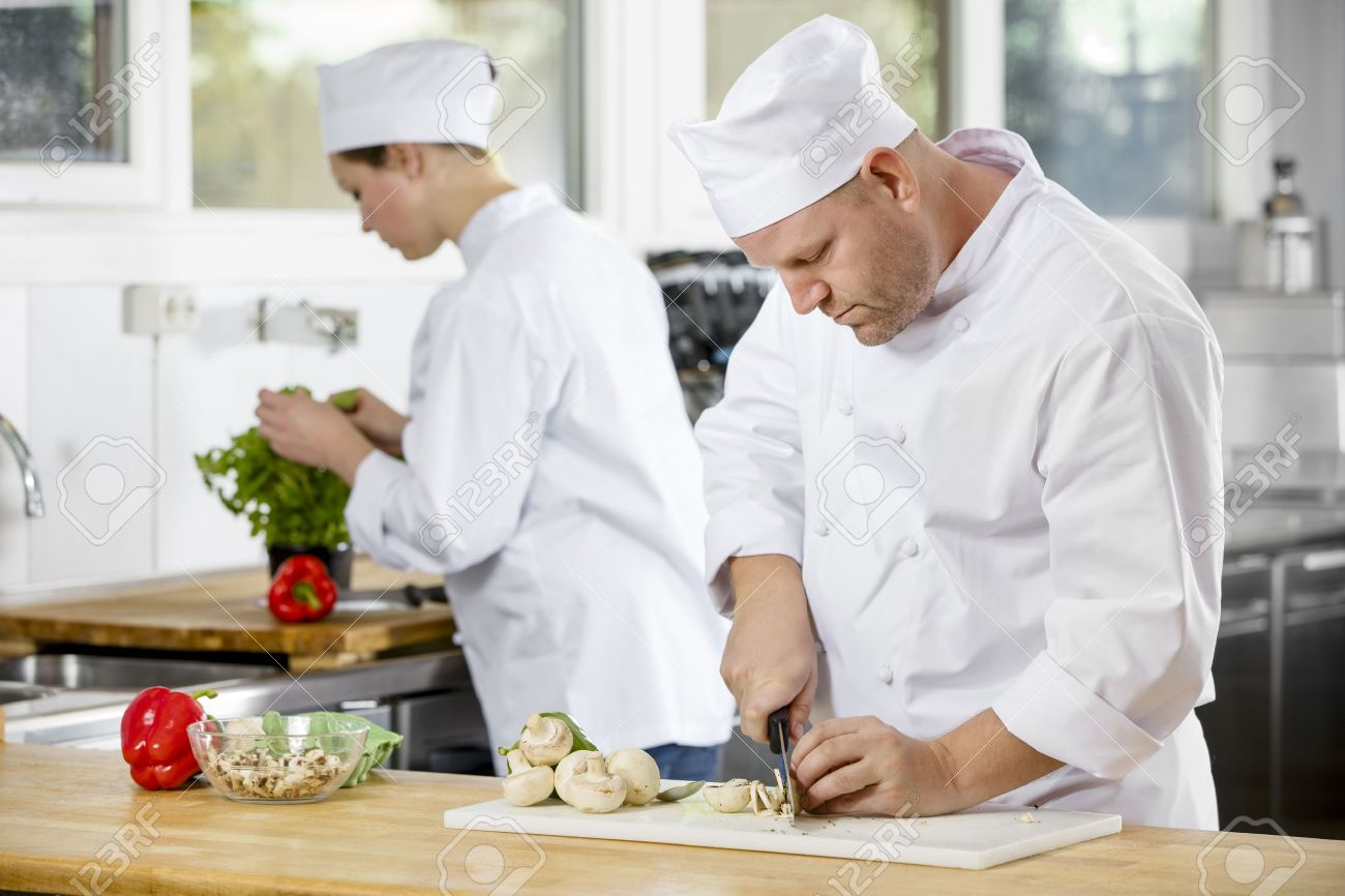 Professional chef chops up mushrooms and makes food in industrial kitchen. Stock Photo - 47050516