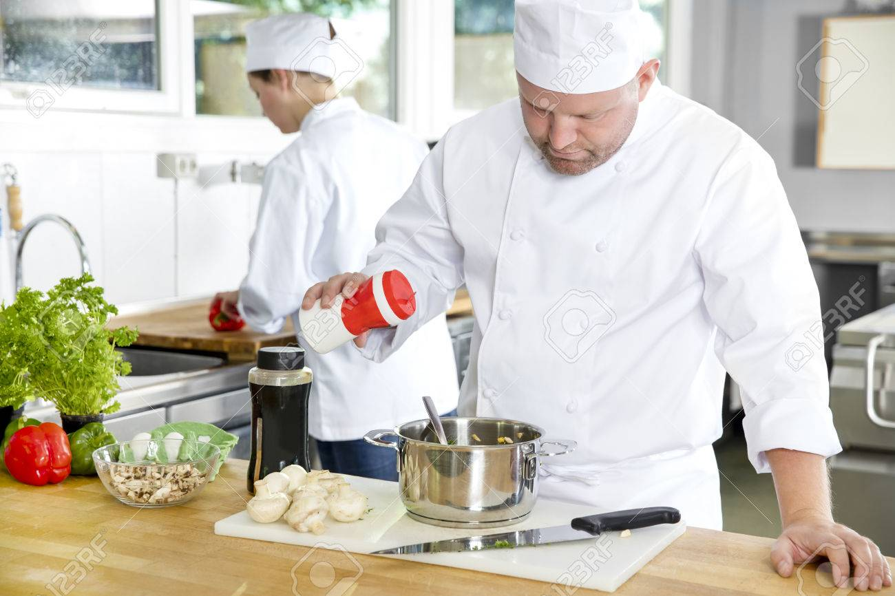 Professional Chef Add Salt In Food At A Industrial Kitchen In ...