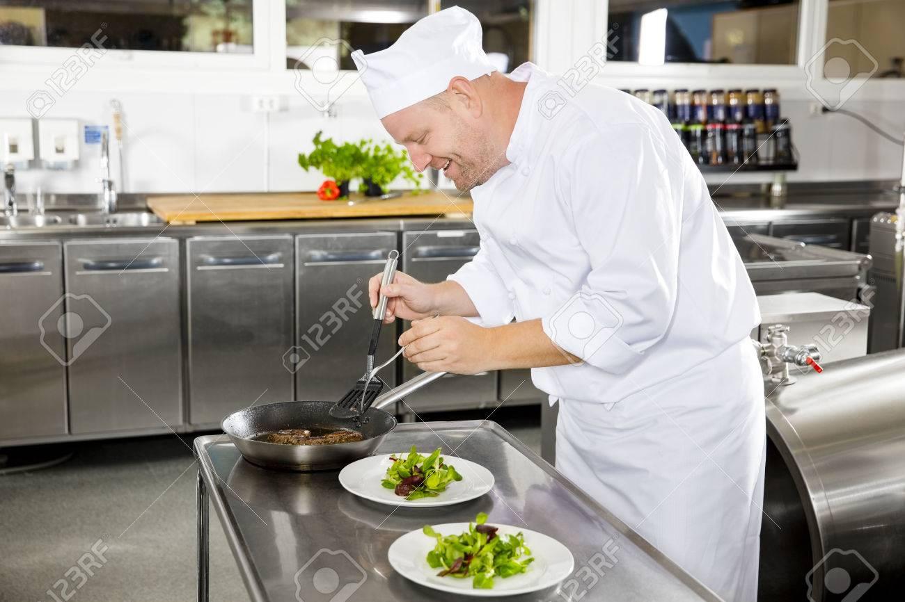 chef professionnel heureux prépare plat de viande de boeuf dans une