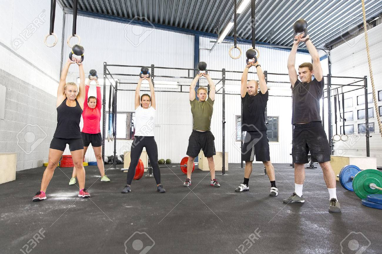Group training with personal trainer and instructor at a fitness center. Kettlebell weight workout at the gym. Stock Photo - 53535029