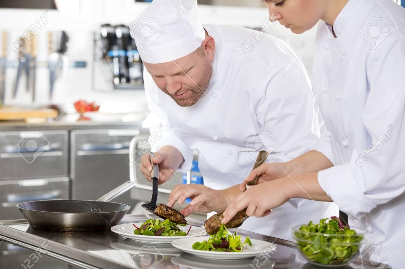 chef enthousiaste prépare plat de viande dans une cuisine