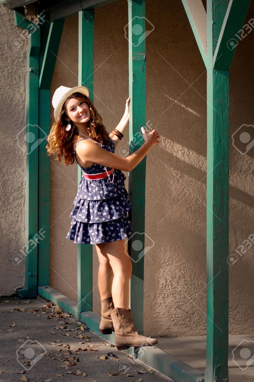 A Pretty Girl In A Short Blue Dress, A Hat, And Boots, Outside ...