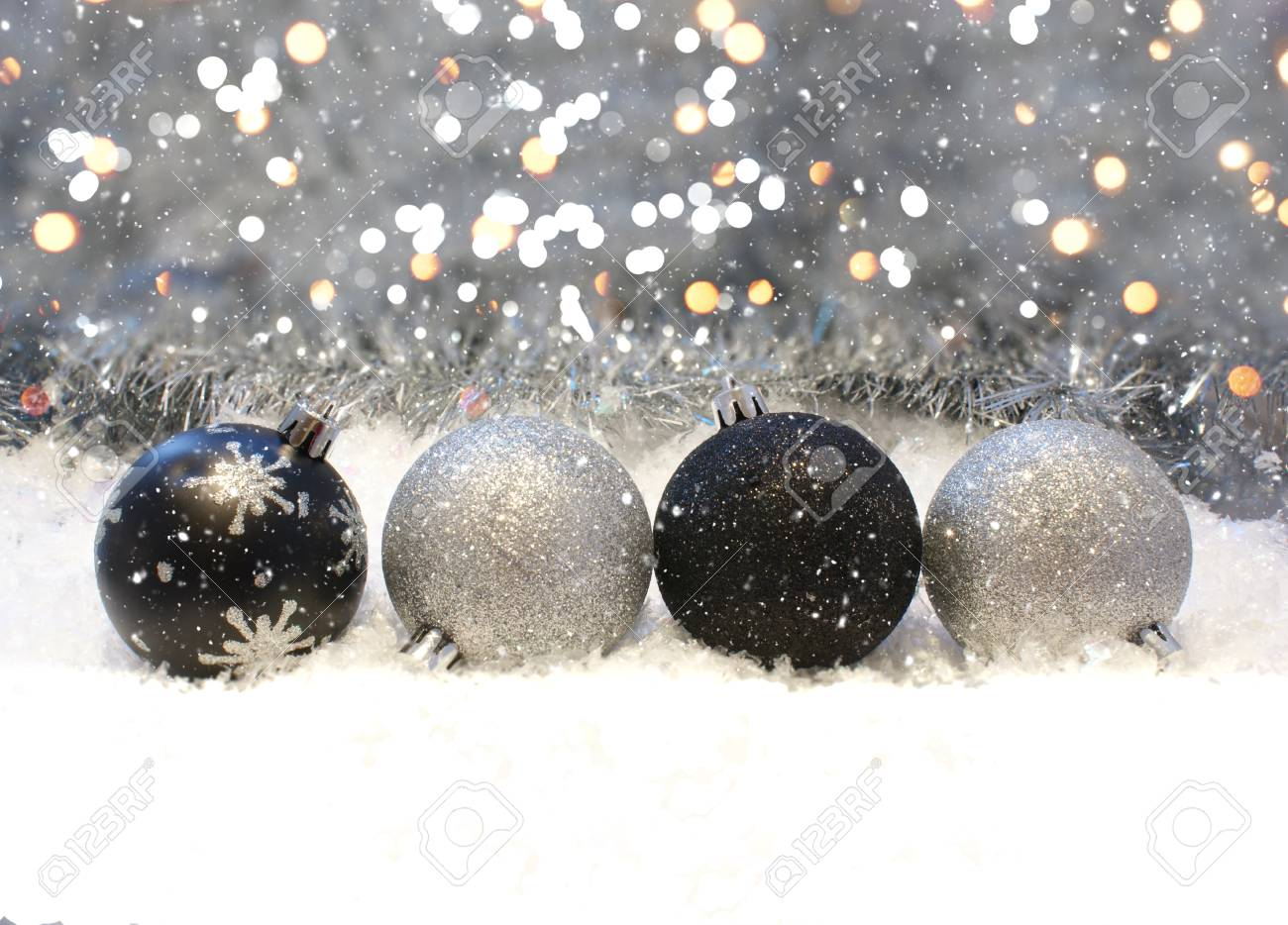 silver and black christmas decorations nestled in snow stock photo 47499926