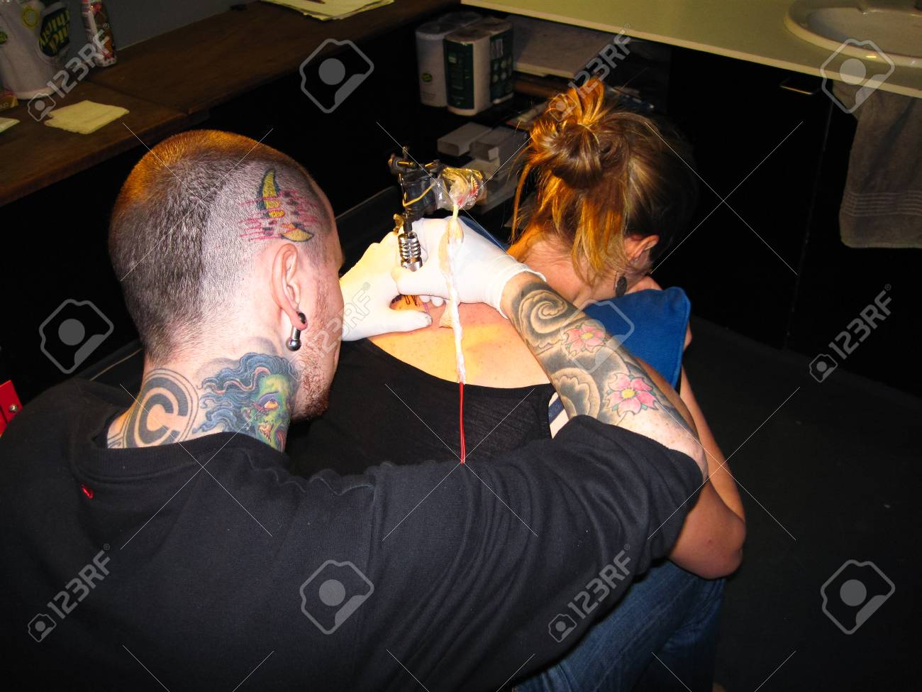 b4128f013 A tattoo artist carefully inks a client in a professional tattoo parlor.  Stock Photo -