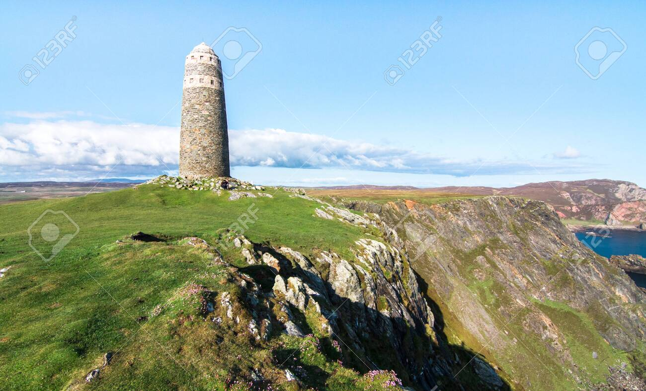 A large rock tower sits on a grassy field at the tip of the Oa Peninsula on the island of Islay in Scotland. - 120150809