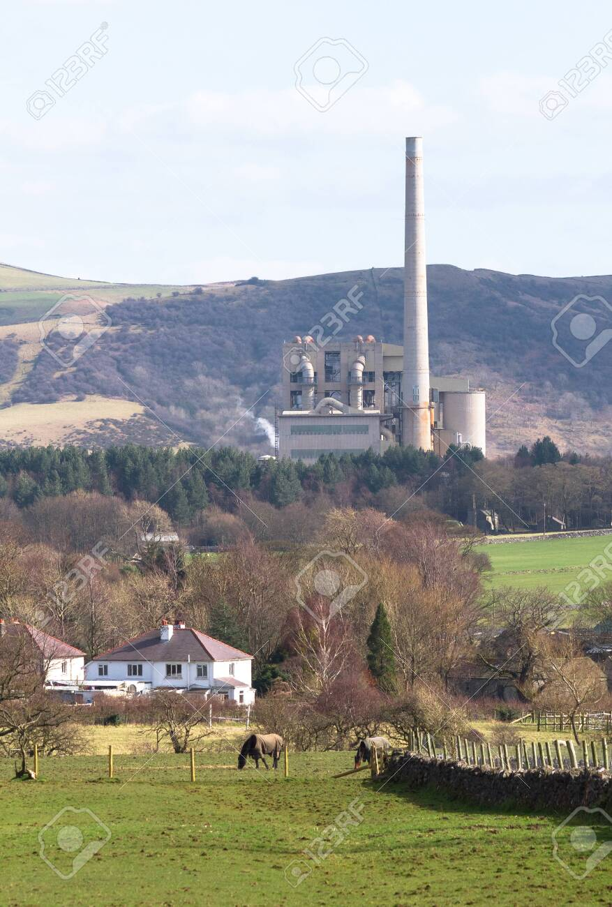 A large factory with a very tall smoke tower sits among agricultural fields in the Peak District, England. - 120579856