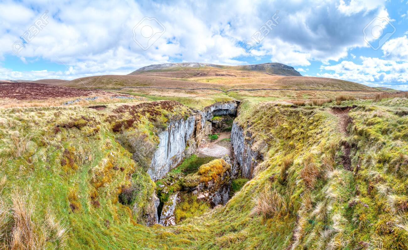 A large rock chasm with massive cliffs in a barren grassy landscape is seen below the peak of Pen-y-Ghent in the Peak District, England. - 120581638