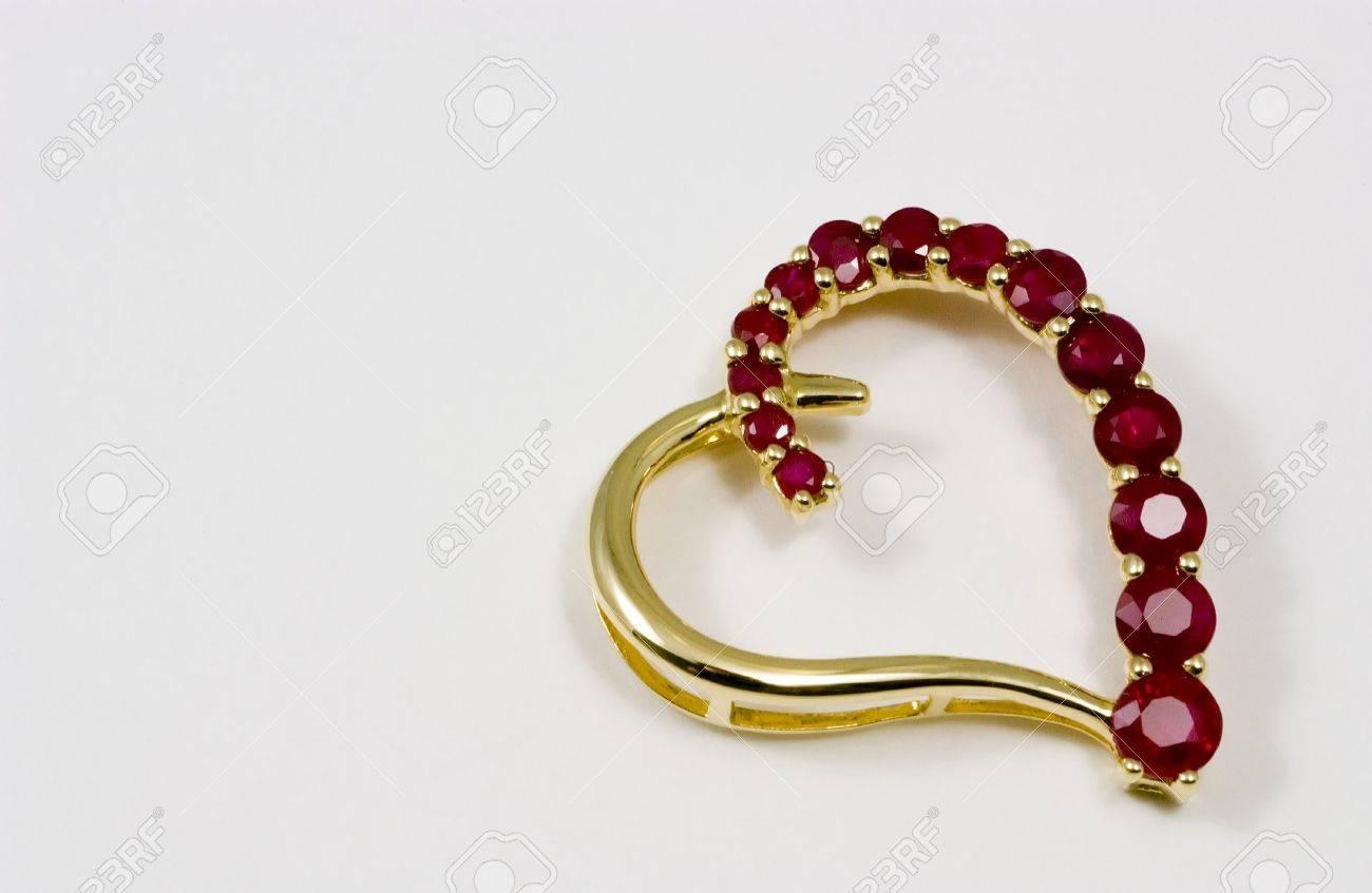 Gold heart shaped pendant with little rubies forming one side gold heart shaped pendant with little rubies forming one side of the heart stock photo aloadofball Choice Image