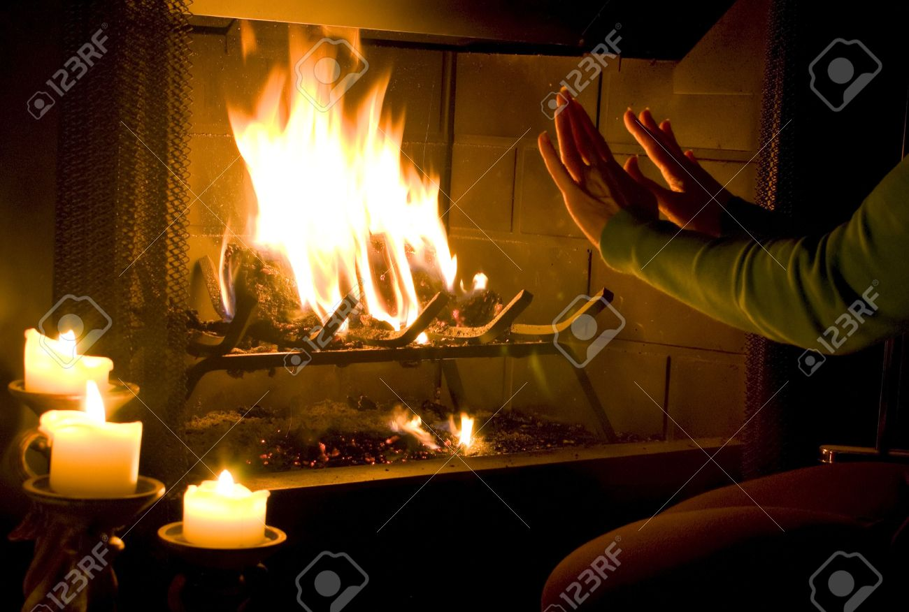 A woman warming her hands by a roaring fire with  candles lit to add to the ambiance. Stock Photo - 1230537