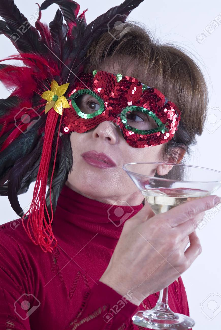 A woman in a colorful, sequined, and featherd mask holding a martini glass as if at a party. Stock Photo - 1615374