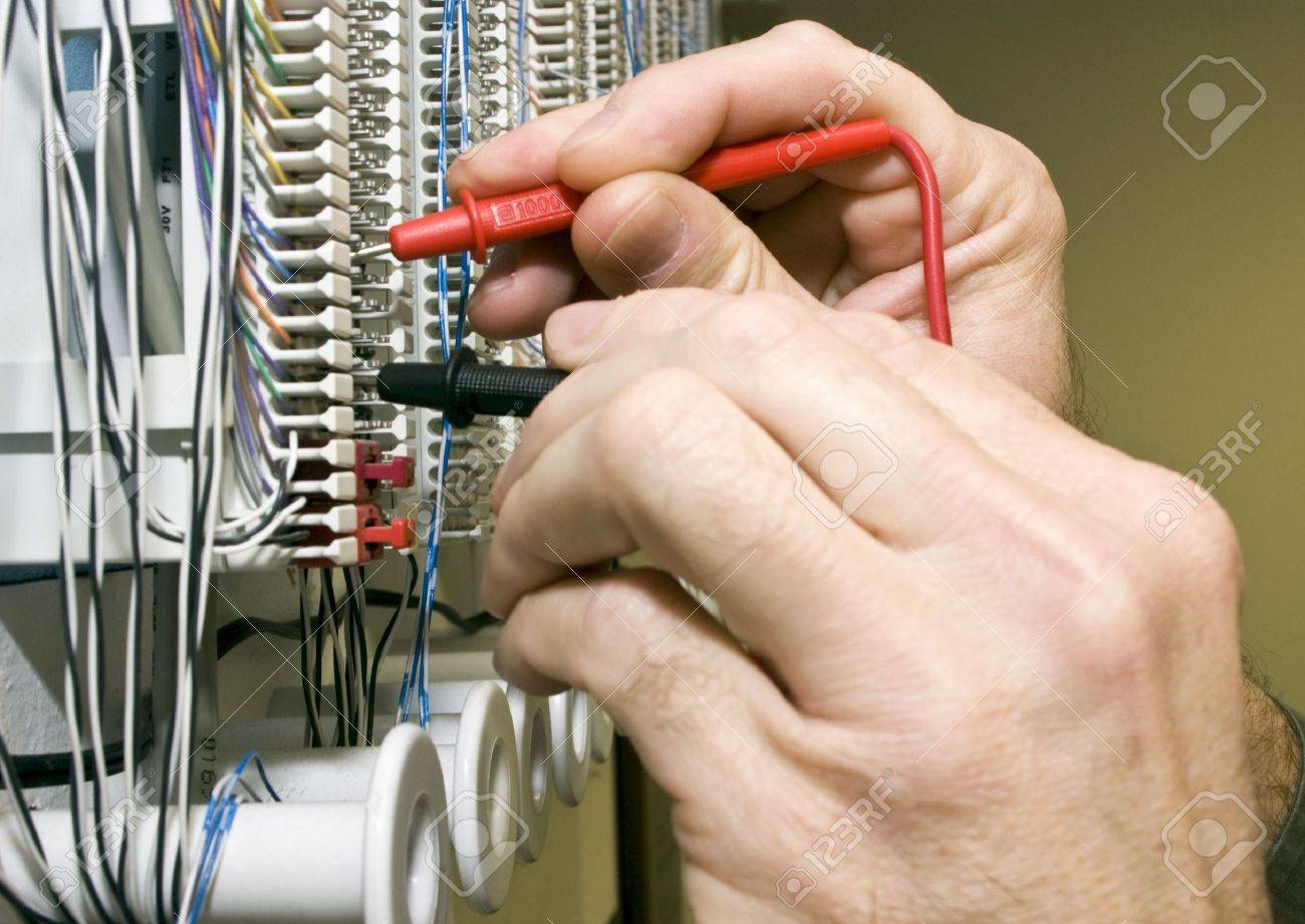 A man testing the voltage on a telephone punch block. Stock Photo - 2712283