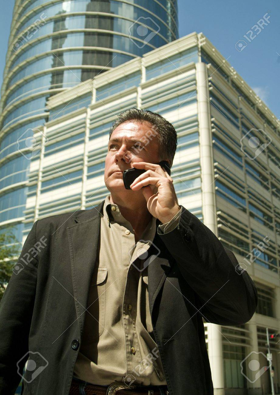 A man talking on a cell phone with large buildings in the back ground. Stock Photo - 2850603