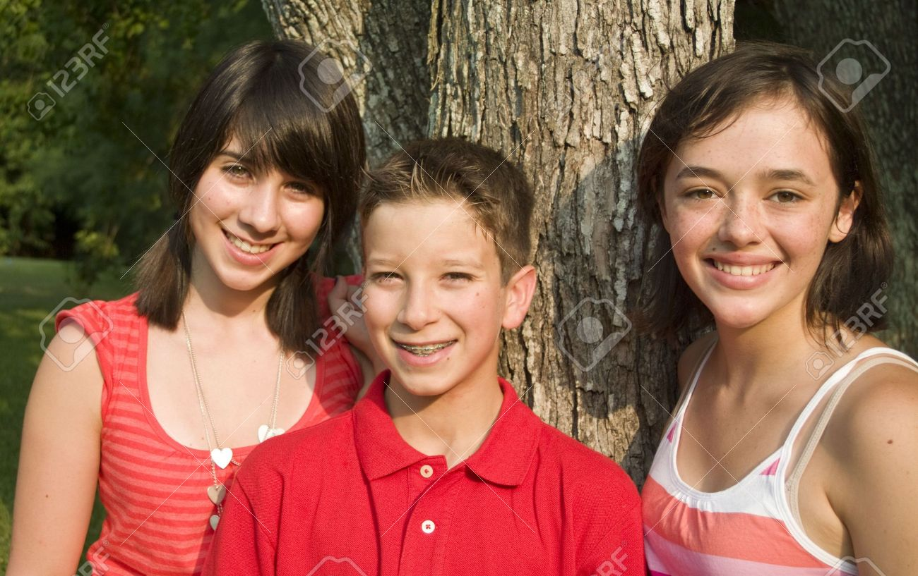 pre teens Three happy teens or pre-teens standing by a tree in the late afternoon sun