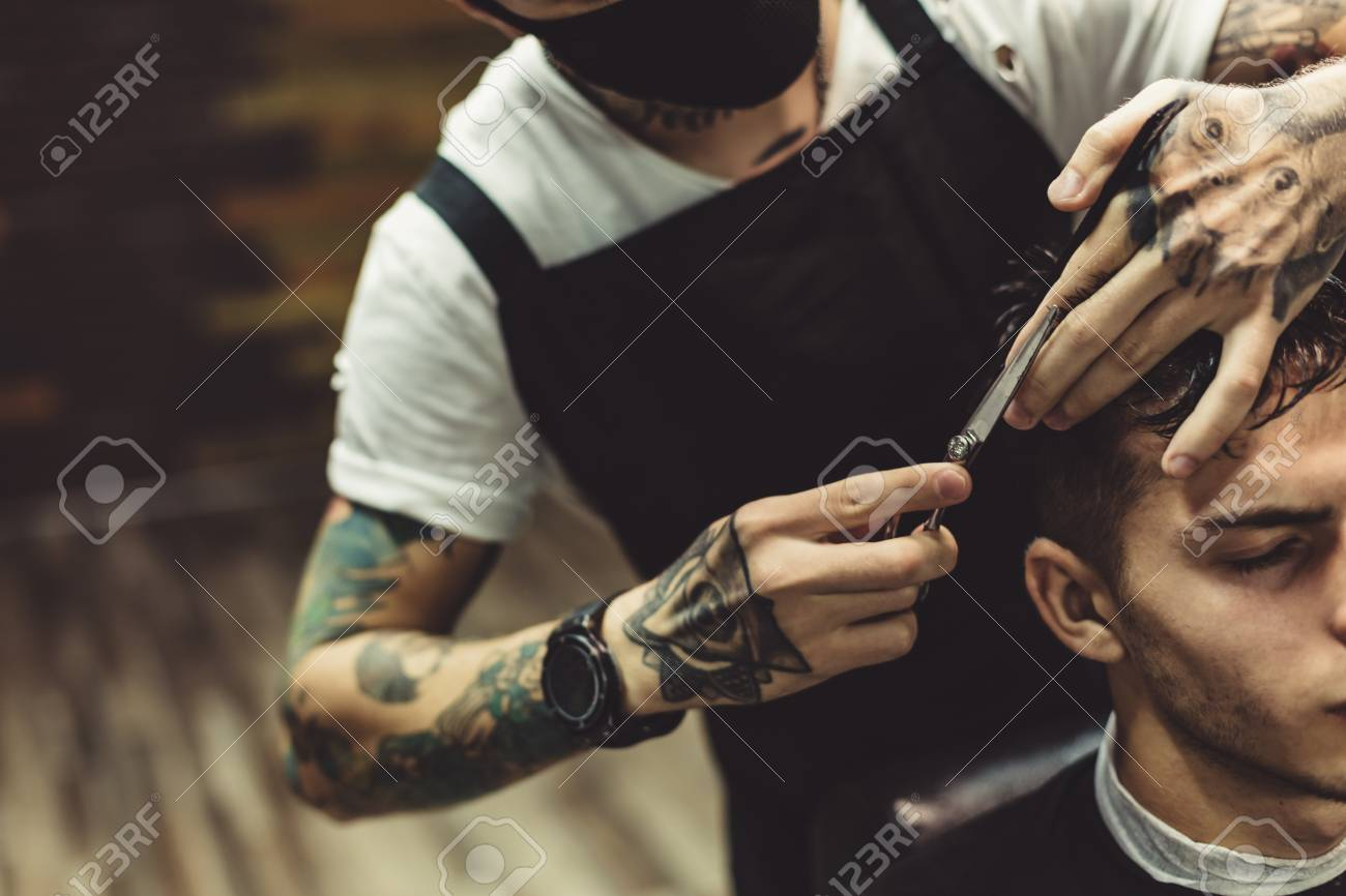 Anonymous Stylish Barber With Tattoos Cutting Hair Of Male Client