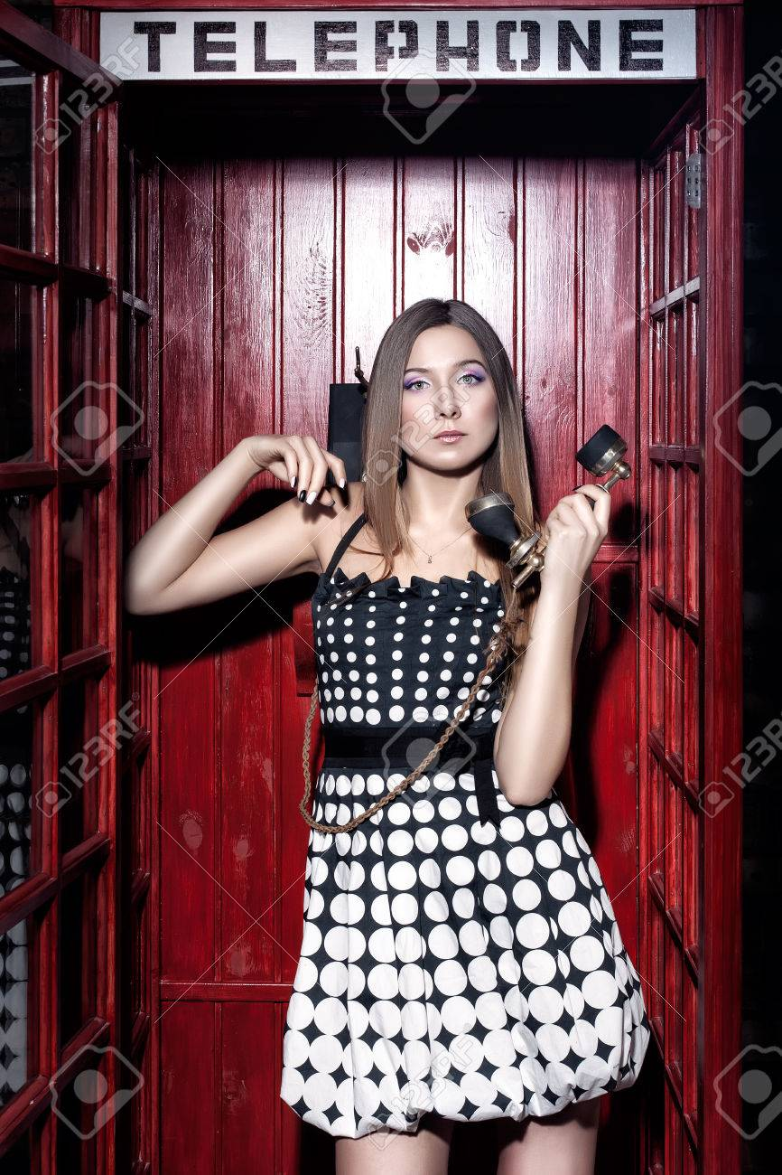 Girl in telephone booth talking on the phone in a retro style Stock Photo - 26562246