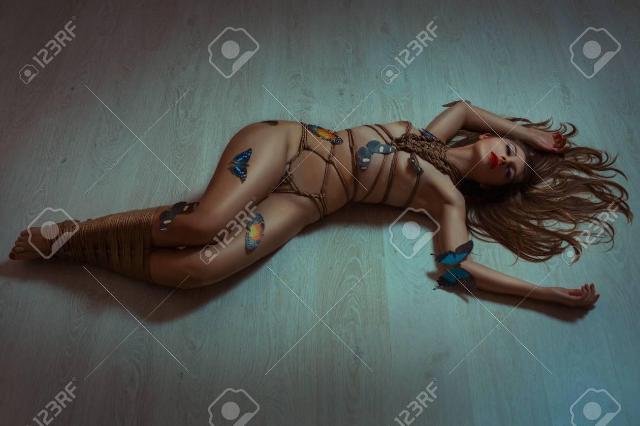 Atadas Desnudas tendido en el suelo mujer desnuda atada con cuerda shibari como arte. foto  artístico tonificado.