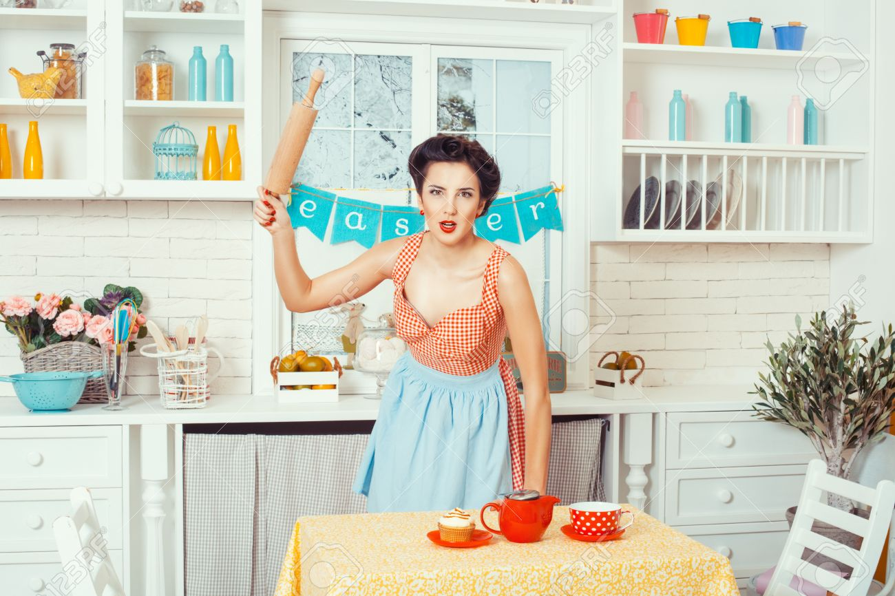 Pin-up Girl Style. Girl Standing In The Kitchen And Brandishing ...