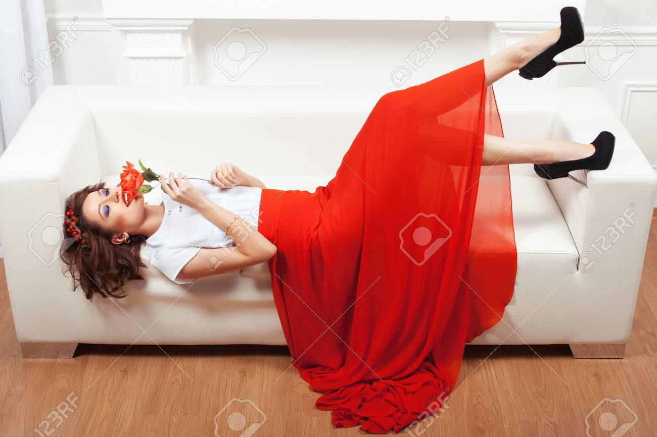 Girl In Red Dress Lying On A White Sofa. She Put A Rose To His