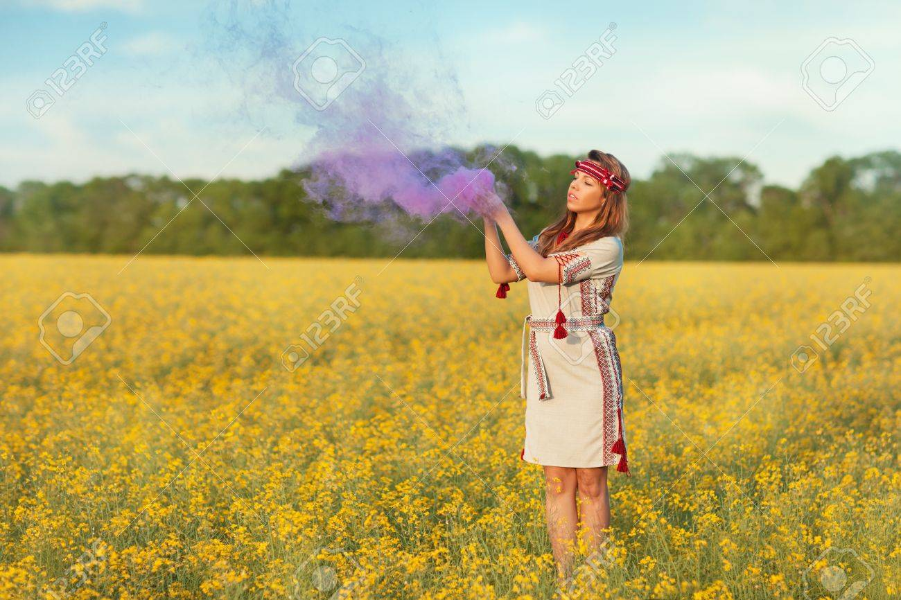 A Girl Stands In A Field Of Yellow Flowers She Raised Her Hands