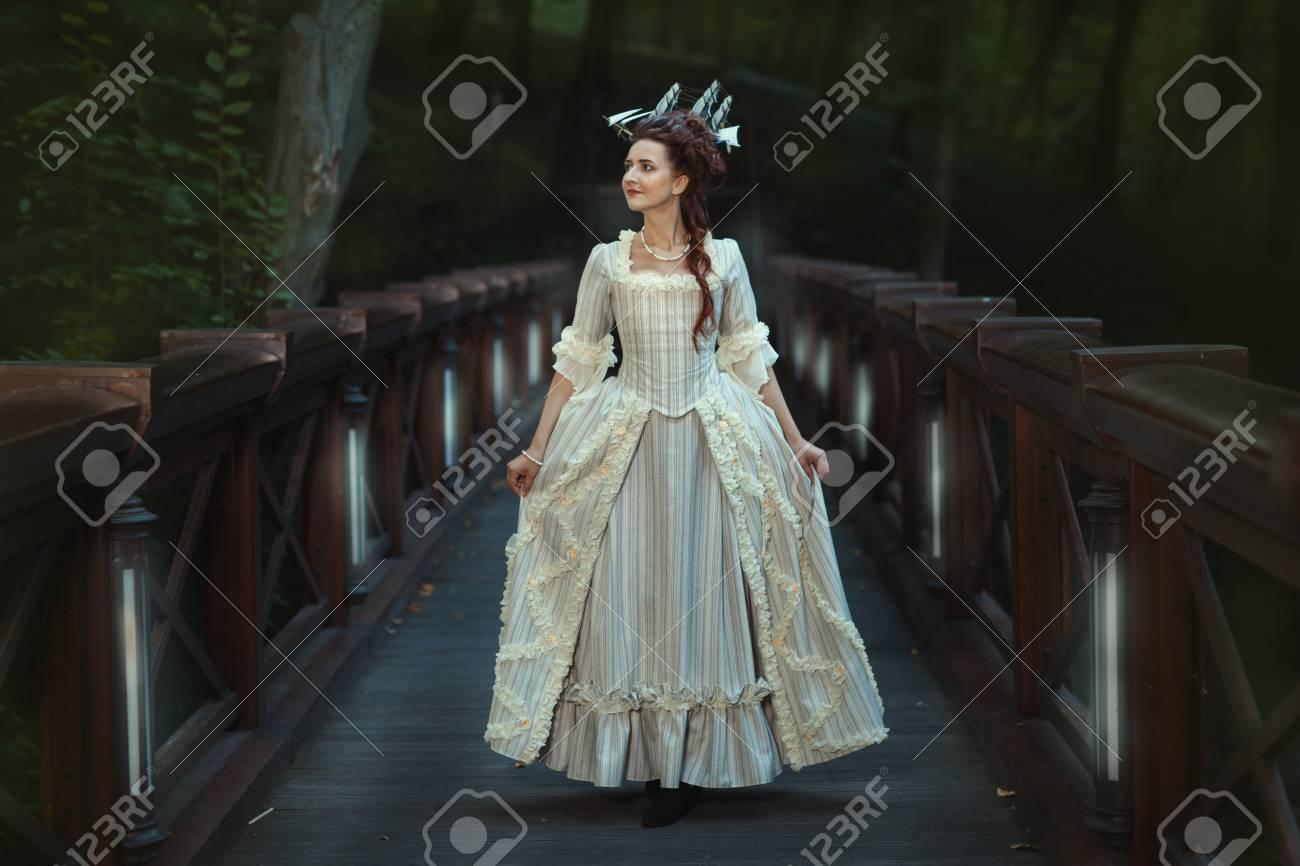 The Girl In An Old Ball Dress Walking On Bridge. Beautiful Vintage ...