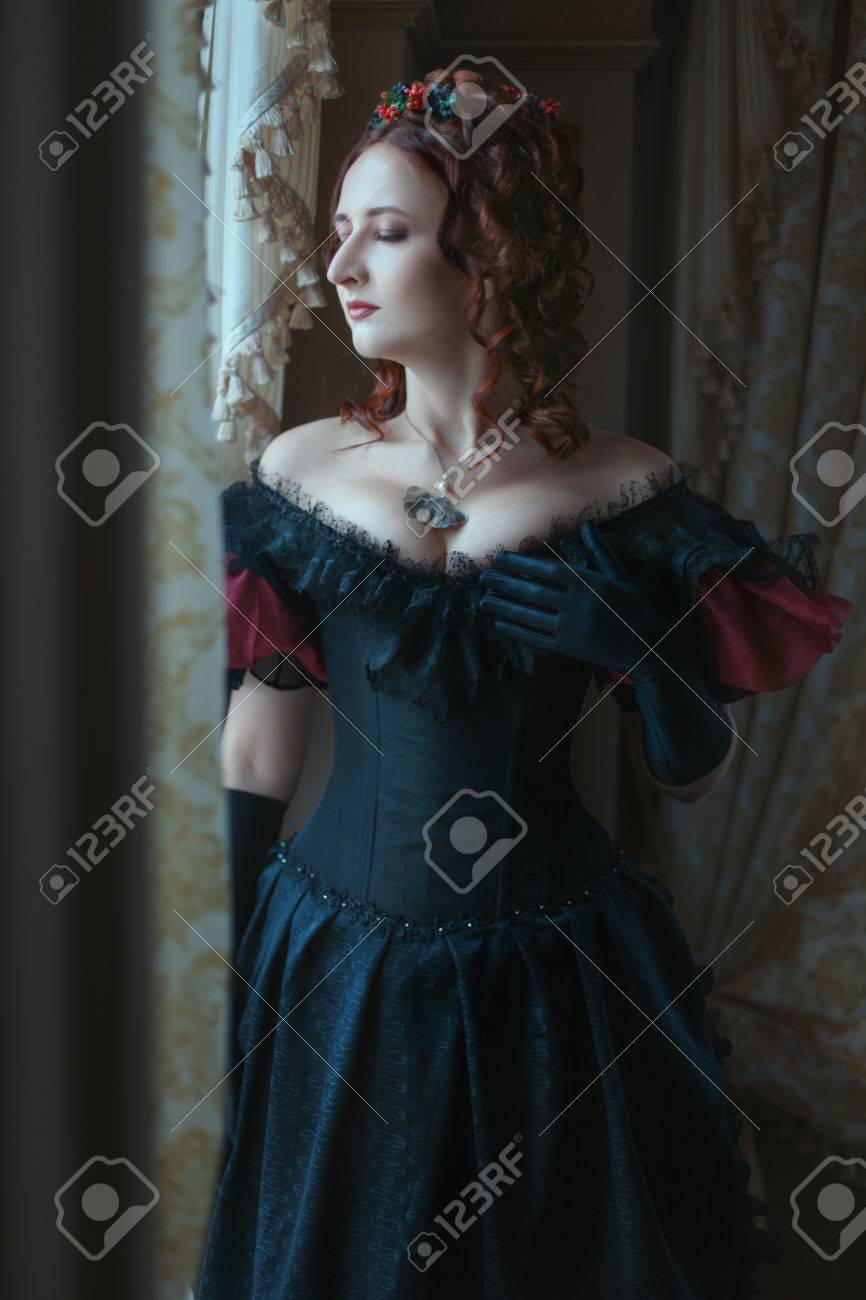 b1d0141ea1d Woman in Victorian dress standing at the window.