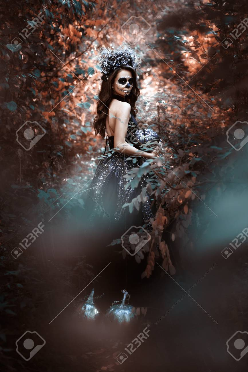 Portrait of a young woman in costume for Halloween in a fairy forest. - 117217213