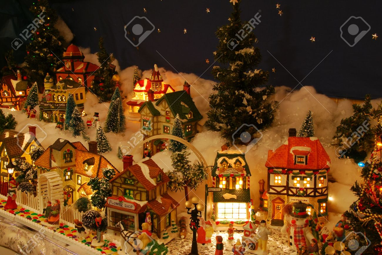 a miniature christmas village is lit up the little people are all about involved in - Miniature Christmas Village