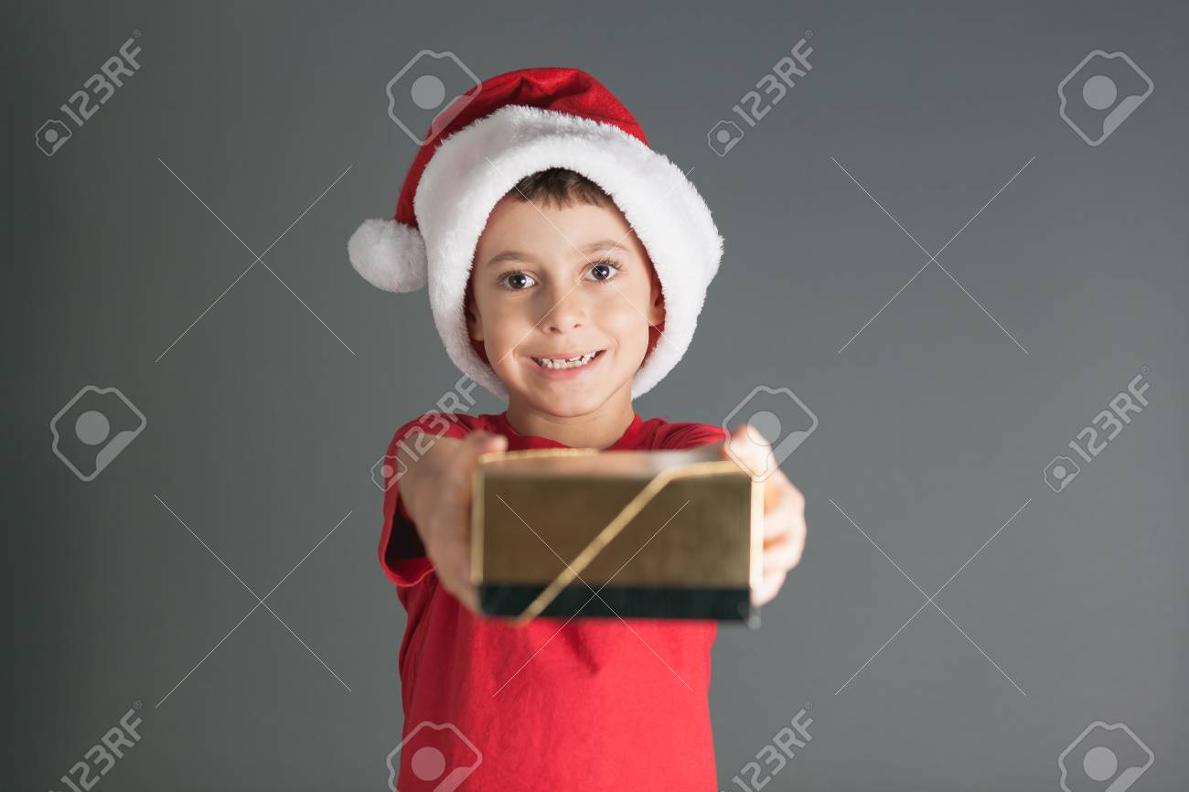 8093a419bdc4e Smiling funny child in Santa red hat holding Christmas gift in hand.  Christmas concept Stock