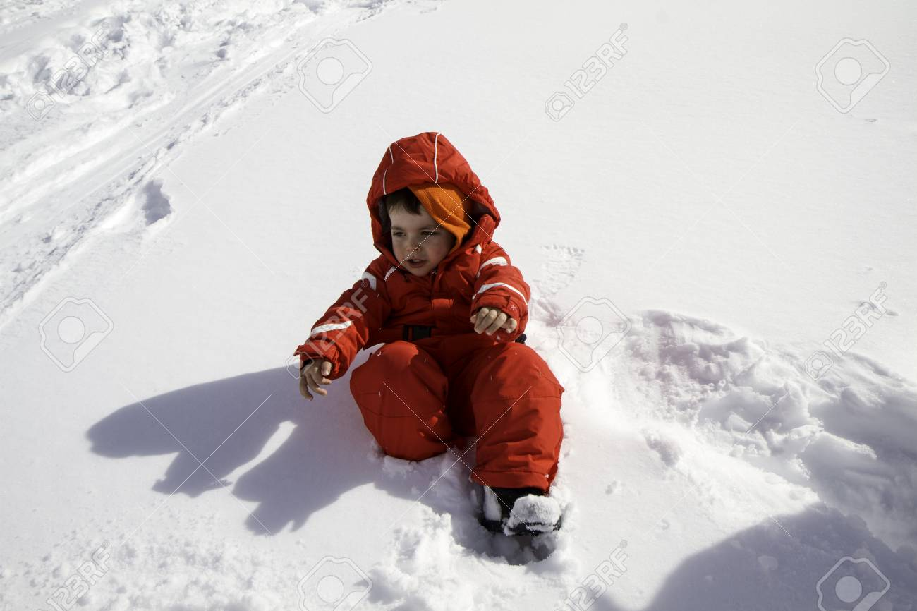418674231430 Close Up Child With Red Ski Suit In The Snow Stock Photo