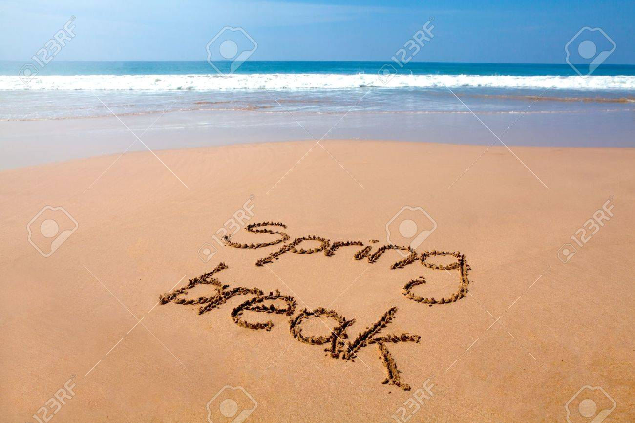 Words spring break written in sand on a tropical beach, with sea in background Stock Photo - 17959593