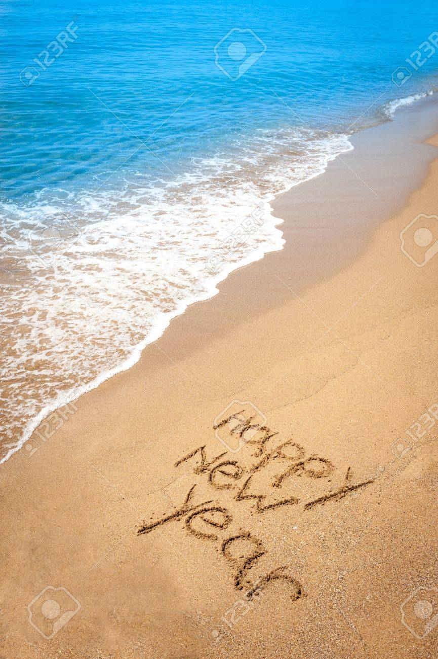 happy new year written in sand on tropical beach stock photo 19620089
