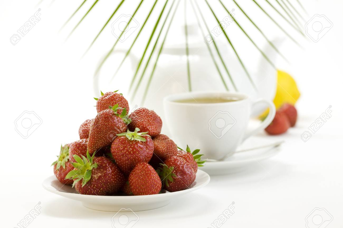 strawberry, lemon, palm leaf, teapot and white teacup with hot tea on white background Stock Photo - 4996473