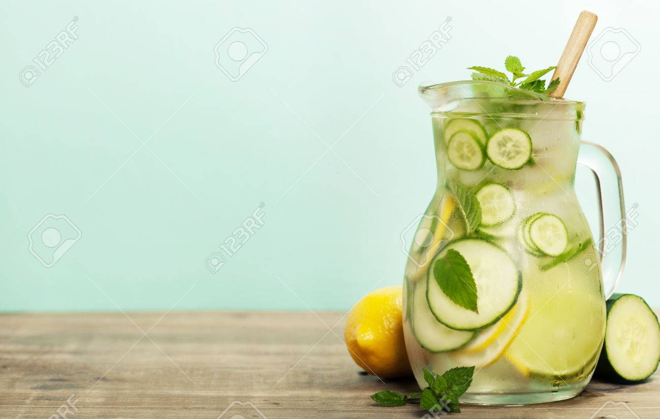 Infused water with cucumber, lemon, lime and mint on blue background - 60810627