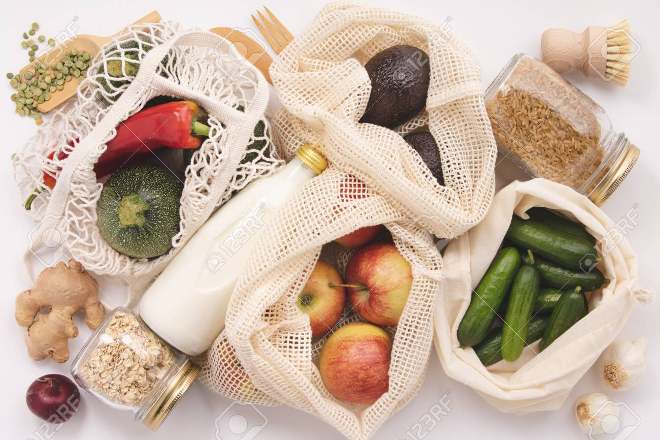 Zero waste concept. Eco bags with fruits and vegetables, glass jars with beans, lentils, pasta. Eco-friendly shopping, flat lay - 121182426
