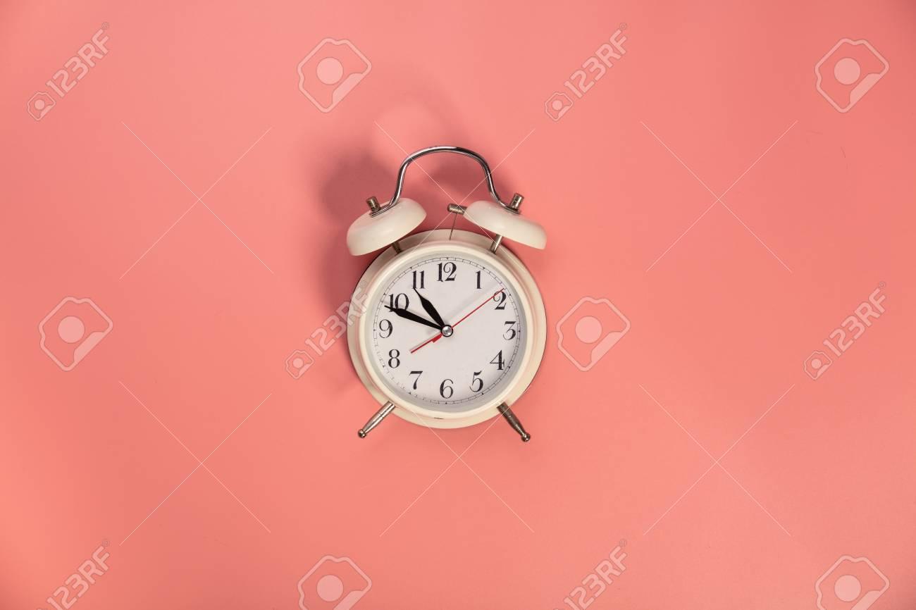 White alarm clock on pink background - flat lay - 124680755