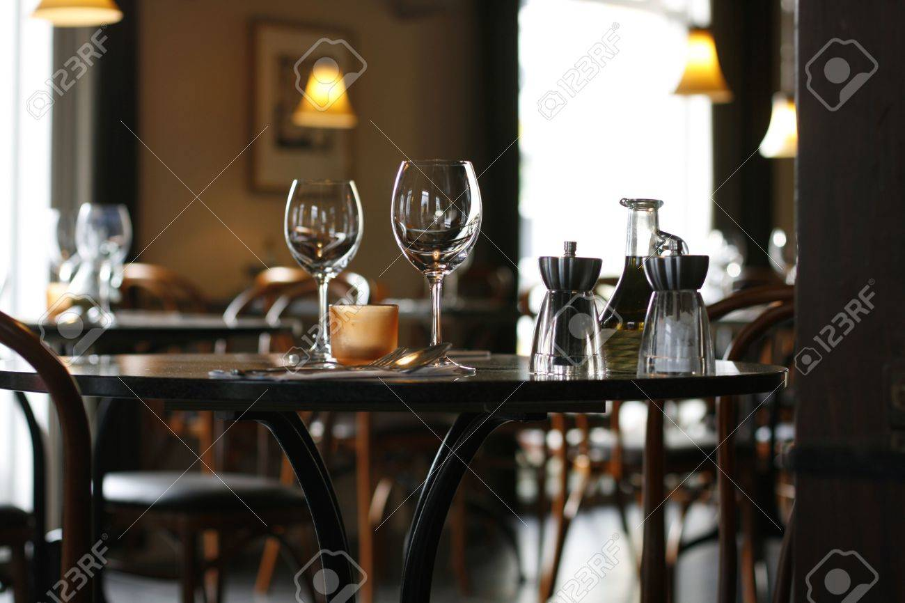 Restaurant table for two - Interior Of A Cozy Restaurant Focusing On A Ready Table For Two Stock Photo 909044