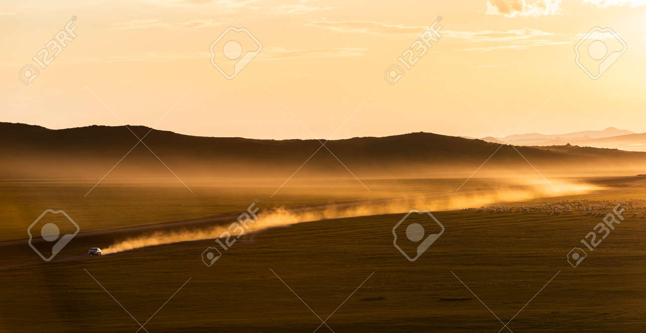Sunset on the steppe of Mongolia with dust and moving car on an unpaved road and mountains in the background. - 166797012