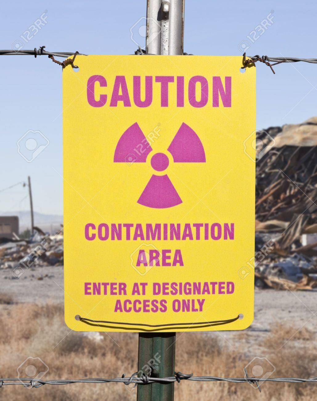 Caution radioactive contamination warning sign with barb wire fence. Stock Photo - 14331492