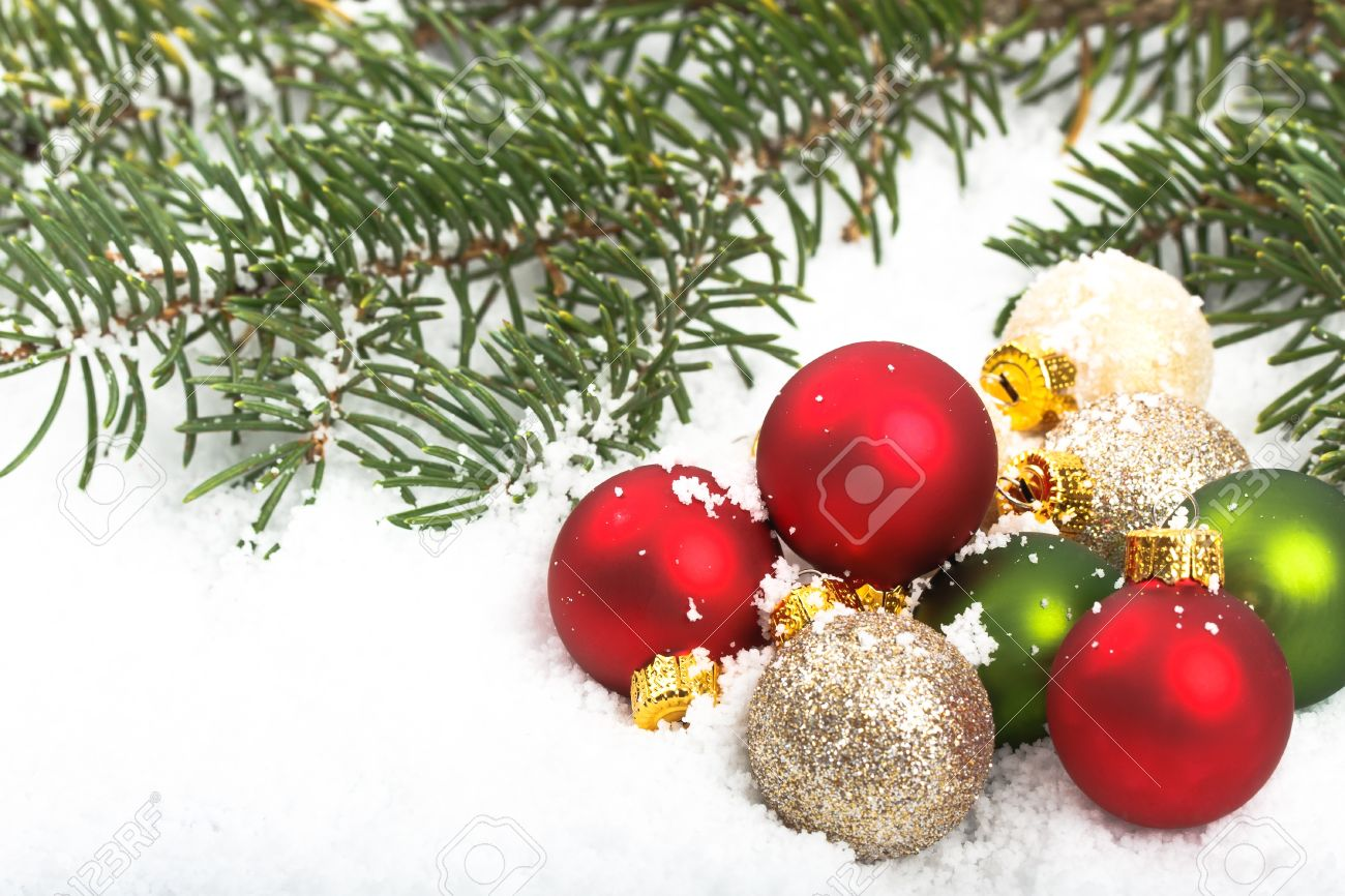 colorful red and green christmas ornaments in the snow with pine boughs in the background stock
